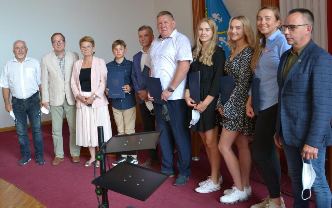 Młodzi sportowcy oraz trener z nagrodami za osiągnięcie wysokich wyników na arenie krajowej i międzynarodowej